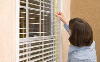Woman measures windows for window coverings.