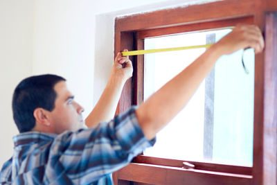 Photo of man measuring a window